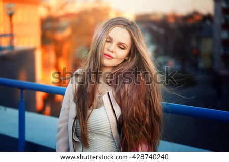 Outdoor portrait of young pretty elegant girl posing at roof at sunset. Lovely soft back light. View on city buildings and roofs.