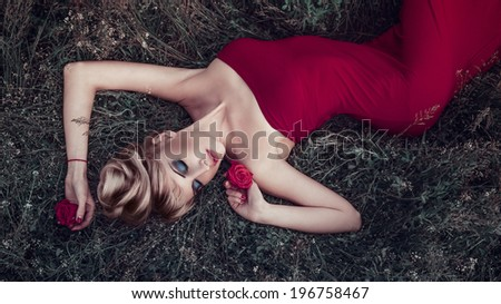 Outdoor portrait of young pretty woman lying on the grass