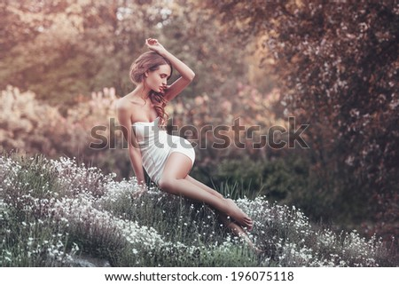 Outdoor portrait of young pretty woman sitting on the field - stock photo