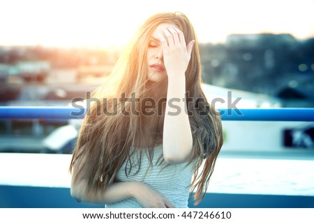 Outdoor portrait of young pretty woman with headache at the end of bright sunset. Lovely soft back light.  - stock photo