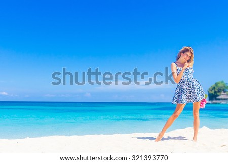 outdoor portrait of young smiling beautiful woman enjoying sunny summer vacation on tropical background