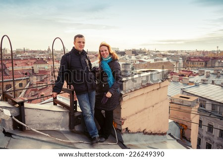 Outdoor portrait of young smiling Caucasian couple on the rooftop in St.Petersburg, Russia. Instagram toned effect - stock photo