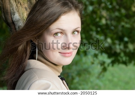 Outdoor portrait of young woman in the autumn park