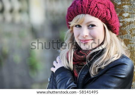 Outdoor Portrait Of Young Woman Leaning Against A Tree - stock photo