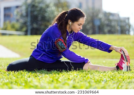 Outdoor portrait of young woman stretching and preparing for running. - stock photo