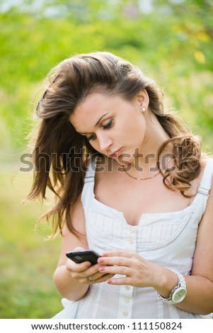 Outdoor portrait of young woman with phone - stock photo
