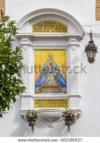 Outdoor public altarpiece of the Virgin Mary painted by Antonio Kiernam Flores, situated on the side of a building in the Plaza Virgin de los Reyes in Seville, Spain.