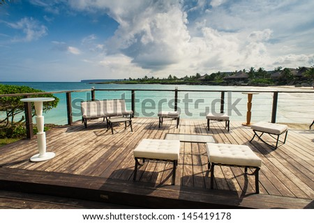 Outdoor restaurant at the beach. Cafe on the beach, ocean and sky. Table setting at tropical beach restaurant. Dominican Republic, Caribbean. Relaxing on remote Paradise beach. - stock photo