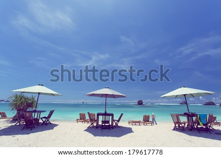 Outdoor restaurant at the beach. Cafe on the beach, ocean and sky. Table setting at tropical beach restaurant. lounge chairs for relaxing and sunbathing - stock photo