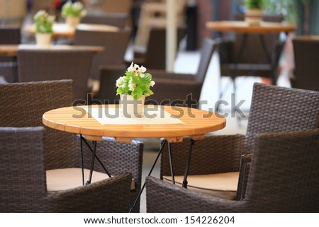 Outdoor restaurant open air cafe chairs with table - stock photo