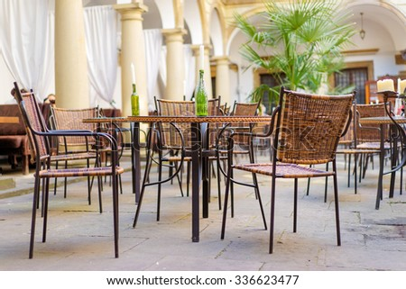 Outdoor restaurant summer terrace - vintage cafe with rattan chairs in old town.