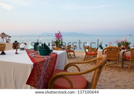 Outdoor restaurant tables, dinner setting at the beach on sunset - stock photo