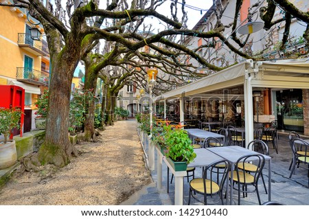 Outdoor restaurant with tables and chairs under tree branches in town of Sirmione, Italy. - stock photo