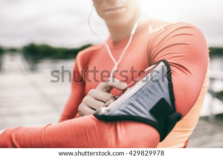 Outdoor runner man tuning his  music player during jogging. Lens flare - stock photo