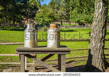 Outdoor rustic rural view with two big milk cans on wooden table board, green grass and trees.Old fashioned rusty metal churns with dents on nature. Your own text or message on milk cans, churns.Sunny