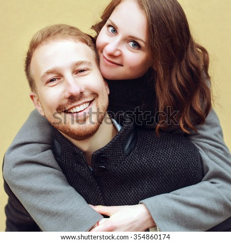 Outdoor sensual closeup portrait of happy young smiling kissing couple in love on yellow background