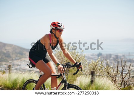 Outdoor shot of a female cyclist riding racing bicycle. Woman cycling on countryside road. Training for competition. - stock photo