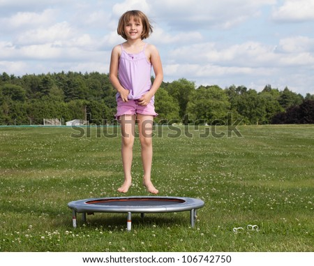 Outdoor shot of a little girl on a trampoline in a field of clover - stock photo
