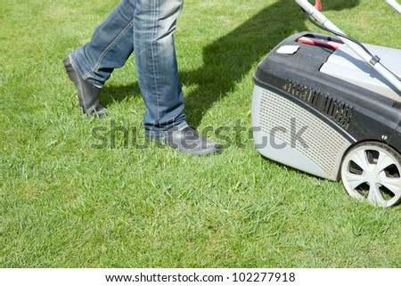 Outdoor shot of a man mowing the lawn on a sunny summer day - stock photo