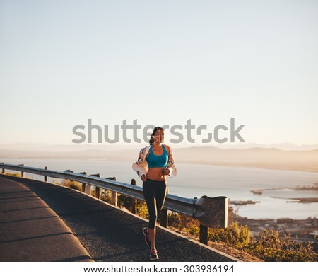 Outdoor shot of a young woman on her morning run. Female athlete running on country road. - stock photo