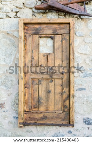 Outdoor shot of an antique door hanging on the wall.