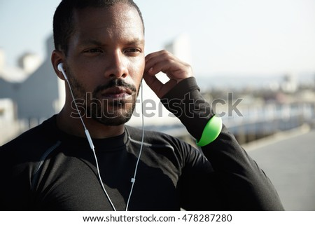 Outdoor shot of attractive muscular male athlete resting after physical activities in open air. Young jogger in black outfit looking into distance, listening to meditative music in earphones