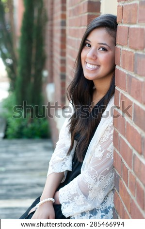 Outdoor shot of beautiful teen with a big smile, sitting in window of brick building. - stock photo