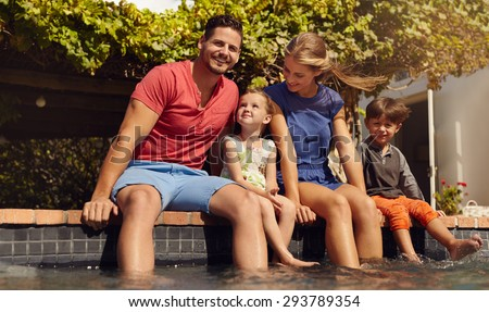 Outdoor shot of beautiful young family sitting next to swimming pool with their feet in water. Young couple with their kids enjoying a hot summer day near pool. - stock photo