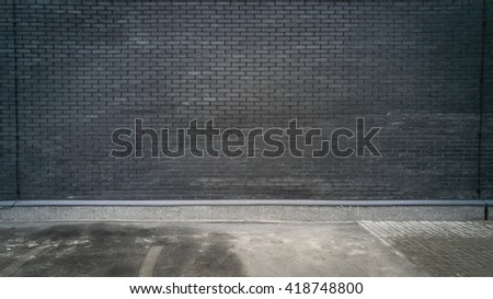 Outdoor shot of black brick wall and concrete floor