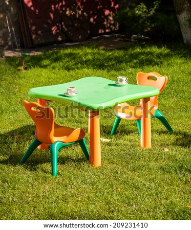 Outdoor shot of children plastic chair and table on grass at yard - stock photo