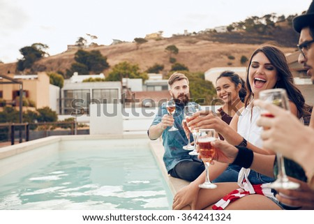 Outdoor shot of happy group of young people sitting on the edge of the pool drinking wine. Multiracial friends enjoying and toasting drinks during a rooftop party. - stock photo