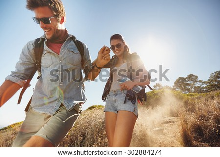 Outdoor shot of happy young couple enjoying on their hiking trip, walking down the mountain trail smiling. Caucasian couple having fun on summer vacation. - stock photo