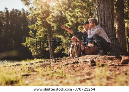 Outdoor shot of senior couple with navigational instruments looking for way in countryside. Mature sitting near a lake during a hike using compass for directions. - stock photo