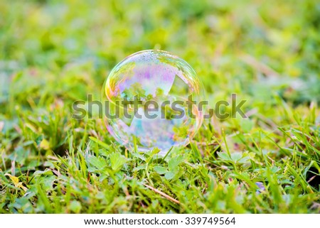 Outdoor shot of soap bubble on the grass - stock photo