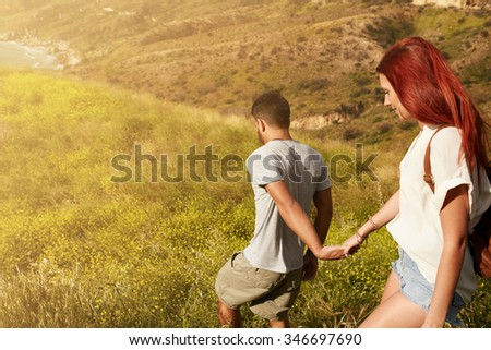 Outdoor shot of young couple enjoying on their vacation, walking down a peak holding hands. Caucasian couple hiking on a summer day. - stock photo