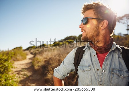 Outdoor shot of young man hiking in nature looking away at a view. Caucasian man enjoying a hike on a sunny day. Copyspace. - stock photo