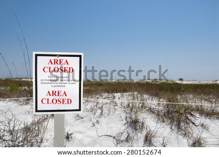 outdoor sign protecting the white sand dunes and sea oat grass at Camp Helen State Park in Panama City Beach Florida along the Gulf of Mexico. Selective focus on the sign.  - stock photo