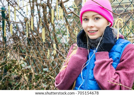 Outdoor sport exercises, sporty outfit ideas. Woman wearing warm sportswear training exercising and listening to music outside during autumn.