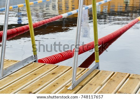 Outdoor sports swimming pool With Blue, White and Red Lap Lines, wooden footbridge, metal stairs in water, without people