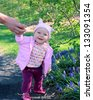 Outdoor spring portrait of a cute little baby girl standing with help - stock photo