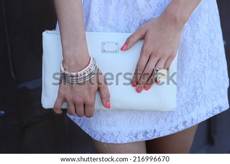 Outdoor stylish girl in white dress with white  handbag clutch tender Accessories - stock photo