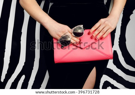 Outdoor stylish girl near striped street wall in black dress with pink handbag clutch - stock photo