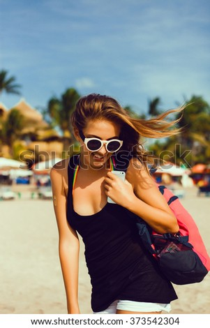 Outdoor summer city evening hipster portrait of young  happy smiling woman having fun outdoor, brunette girl with glasses, a backpack posing,Indonesia the island of Bali, the sand palm trees, close up - stock photo