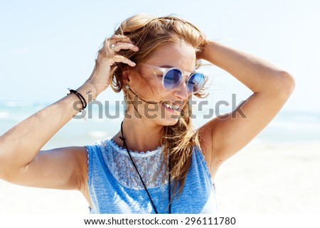 Outdoor summer closeup fashion portrait of young blonde smiling girl