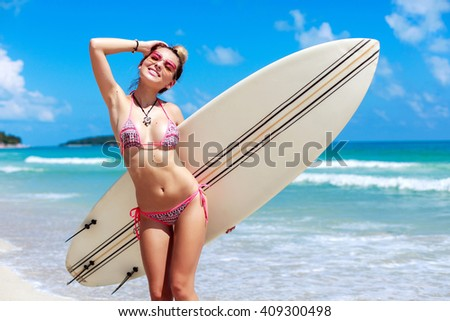 Outdoor summer closeup lifestyle portrait of happy smiling tanned sexy woman posing on the beach with surfboard in bikini and sunglasses