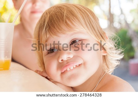 Outdoor summer closeup portrait of funny cute blond Caucasian baby girl with glass of orange juice - stock photo