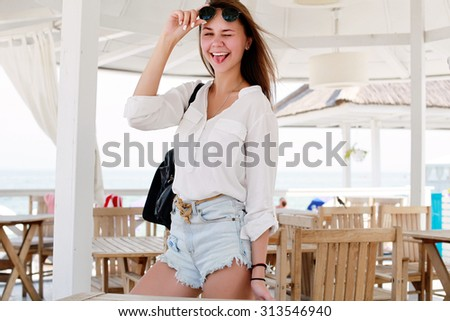 Outdoor summer closeup portrait of funny pretty young smiling girl having fun and going crazy showing tongue