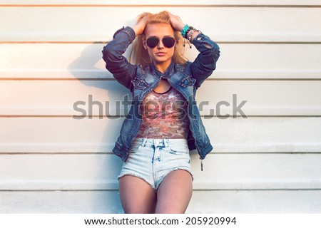 Outdoor summer closeup portrait of young stylish fashion glamorous woman or girl posed in sunny day on street jeans jacket and sunglasses standing near white wall - stock photo