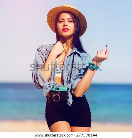 Outdoor summer fashion portrait  of gorgeous sexy woman with perfect tan body, full red lips and long strong legs posing on the  tropical  sunny beach. Wearing  crop top ,  shorts . - stock photo