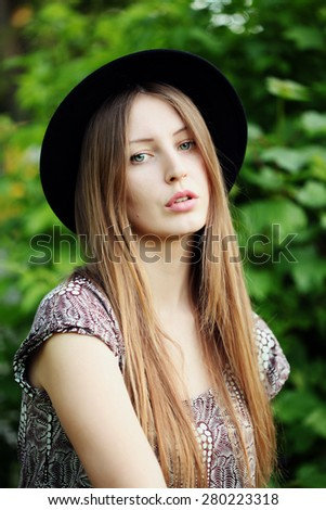 Outdoor summer fashion portrait of young woman wearing boho style clothes enjoy in summer day on the field of grass. Sensual elegant lady wearing hat and hipster outfit